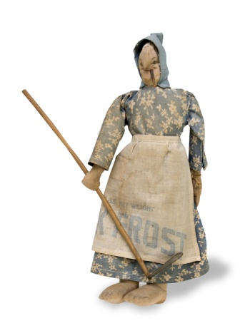 "Depression-era doll holding a hoe and smoking a cigar. Her apron is made from a ""Jack Frost"" sugar bag"