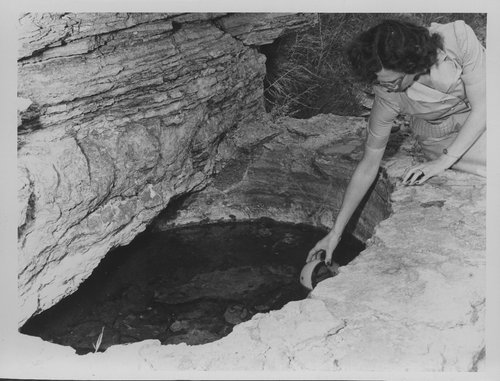 Woman dipping cup into Waconda Springs
