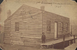 African American child standing outside Leavenworth's first house.