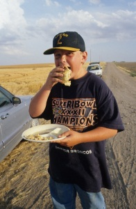 Lucas Smith enjoys a roadside supper near Bird City, 1998.  His family travels from Colorado Springs every summer to help uncle and  aunt Steve and Jan Busse harvest wheat.