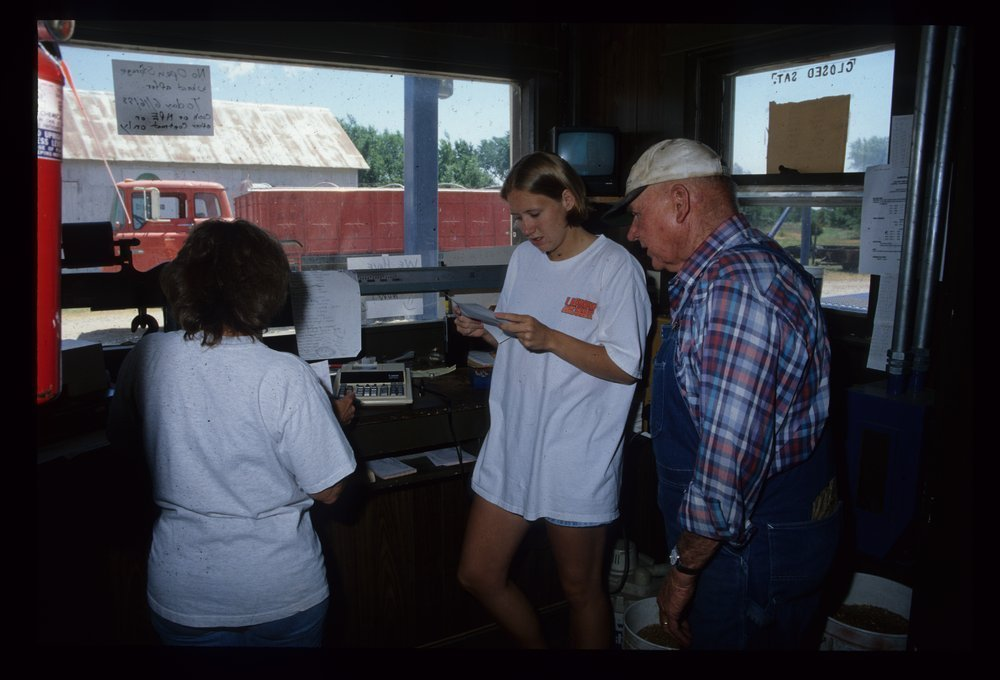 Betty Wallace and Dana Parsons visit with a local farmer in the  Cargill elevator office at Cleveland, 1998.