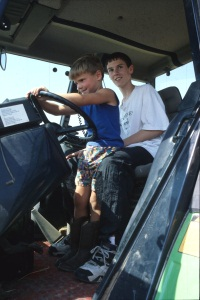 Jason Frey (5) and Derek Young (13), grandsons of Enola and Nelson Dreier, help operate the grain cart, Hesston, 1998.