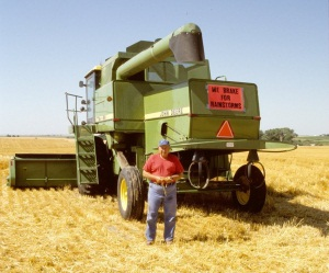 "Ted Thummel of  Esbon takes a wry approach to harvest weather, 1998.  The sign on his  combine reads, ""We brake for rainstorms."""