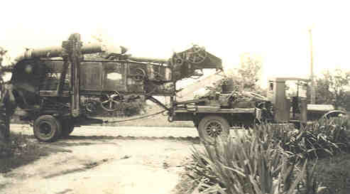 Truck hauling a threshing machine