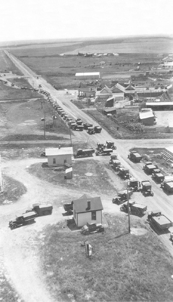 Farm trucks lined up to unload at the three Copeland grain elevators in 1928: Jennings, Security, and Farmer's Co-op.