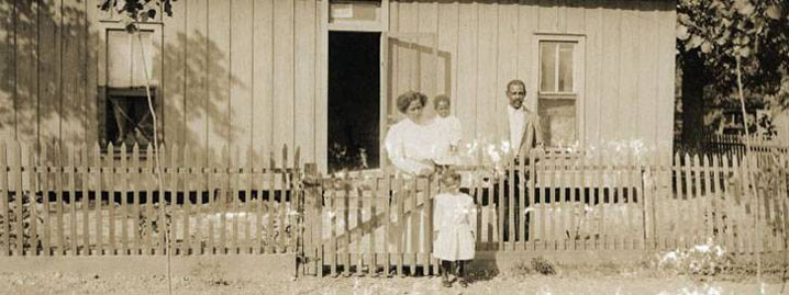 An unidentified family standing in front of their house