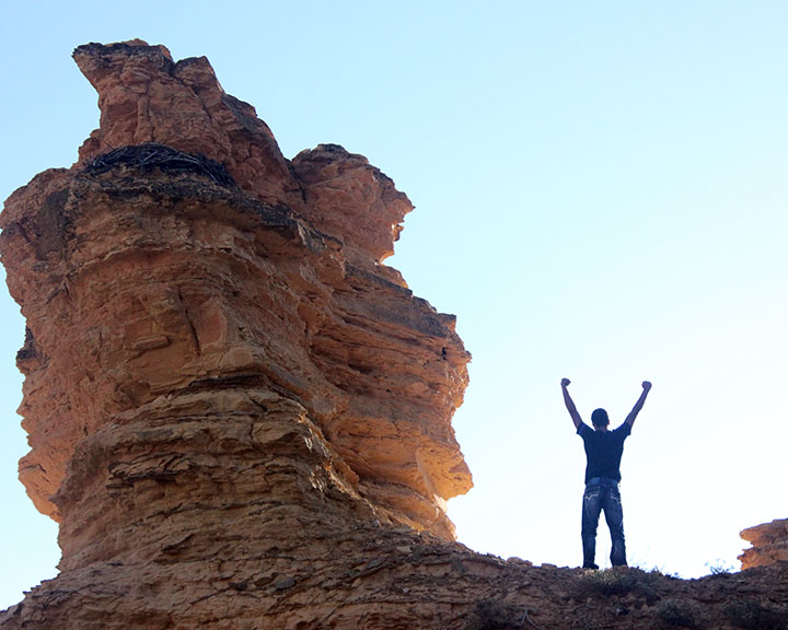 Boy standing beside tall rock formation.