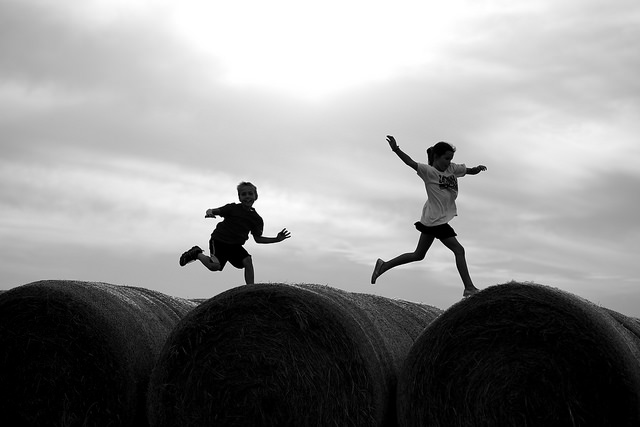 Two kids jumping on hay bales.