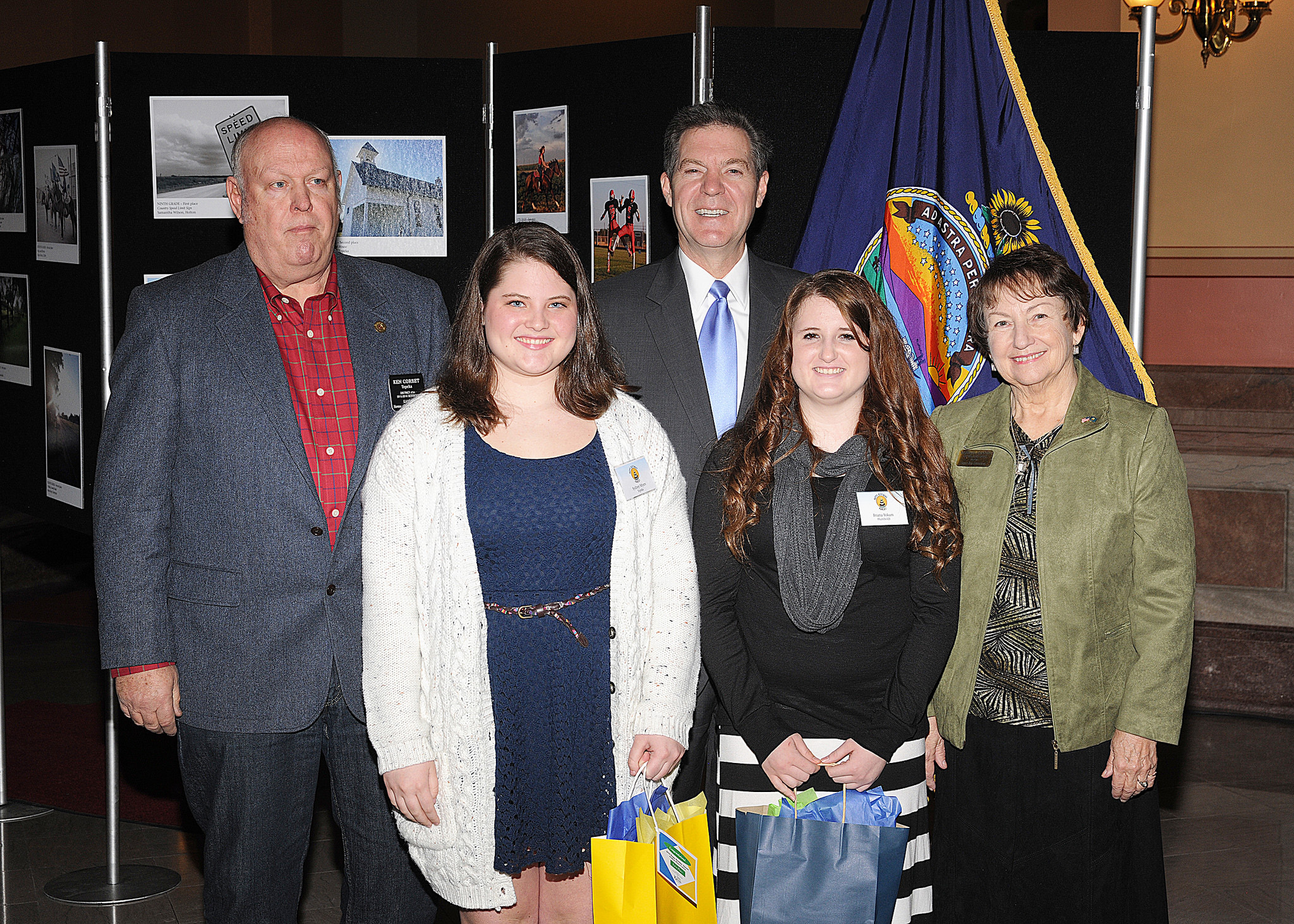 12th grade winners Sydney Myers, Briana Yokum, with Representative Ken Corbet, Governor Sam Brownback, and Marearl Denning
