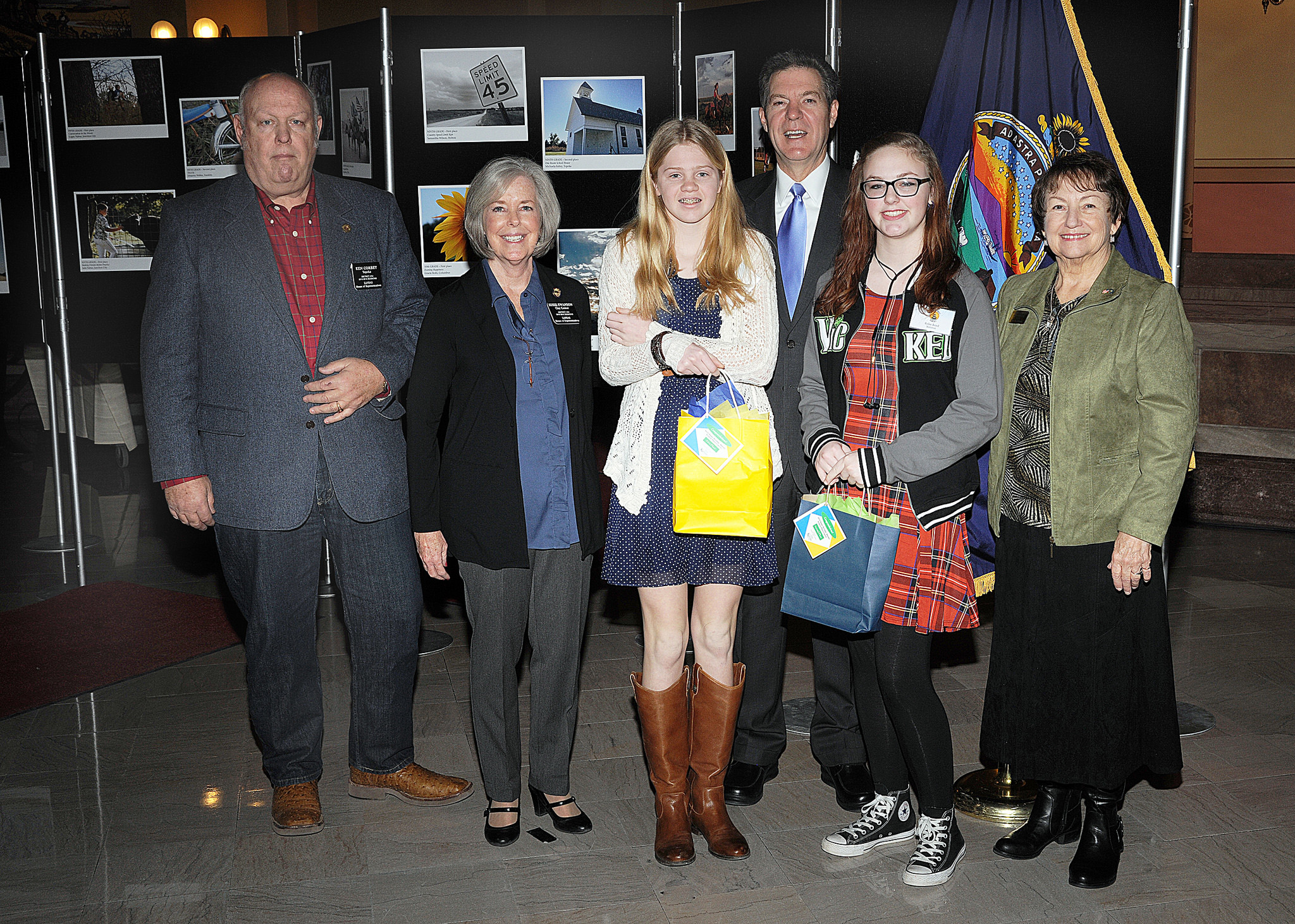 Eighth grade winners Samantha Wilson and Michaela Falley with Representative Ken Corbet, Representative Susie Swanson, Governor Sam Brownback, and Marearl Denning