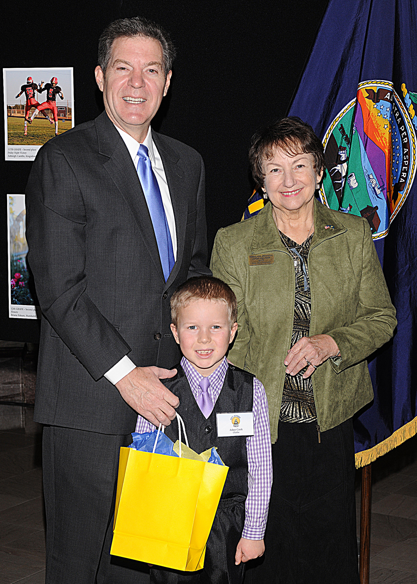 First grade winner Asher Cook with Governor Sam Brownback and Marearl Denning