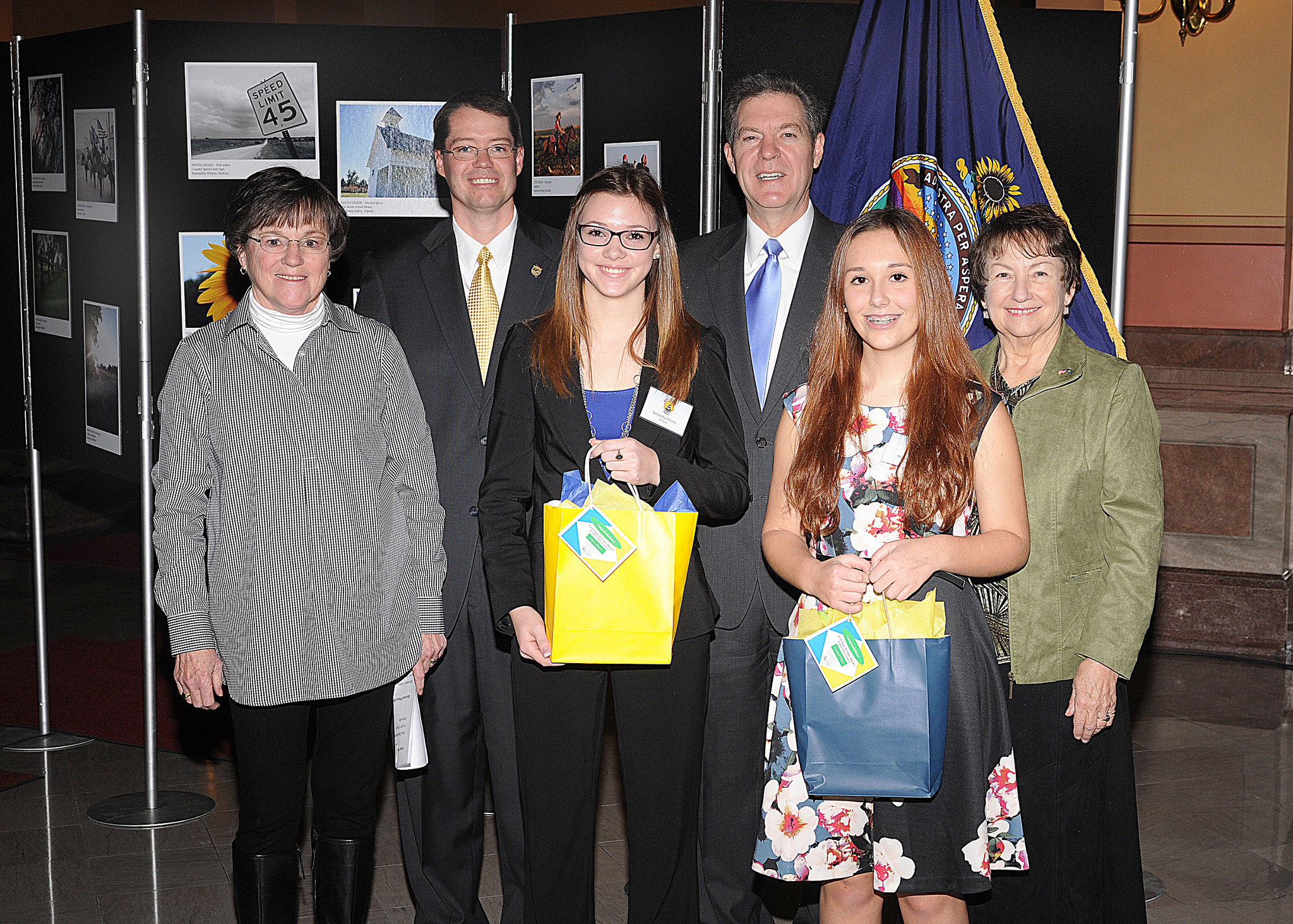 Ninth grade winners Samantha Wilson and Michaela Falley with Senator Laura Kelly, Representative Fred Patton, Governor Sam Brownback, and Marearl Denning