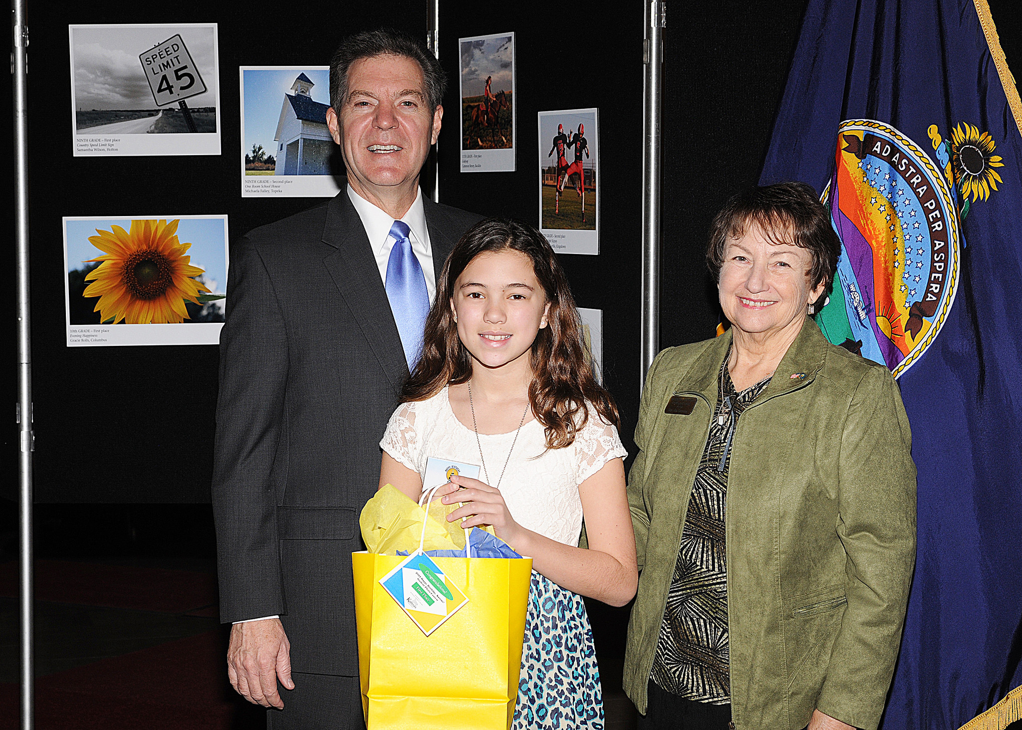 Sixth grade winner Jada Nabus, Maurice Hilbert not pictured, with Govoernor Sam Brownback and Marearl Denning