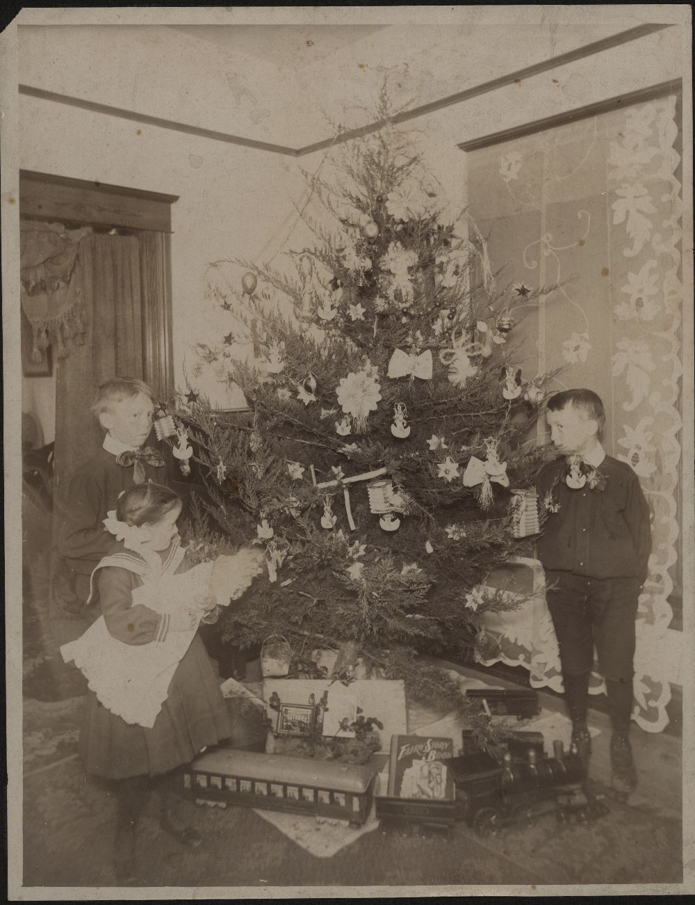 Children around decorated Christmas tree around 1900