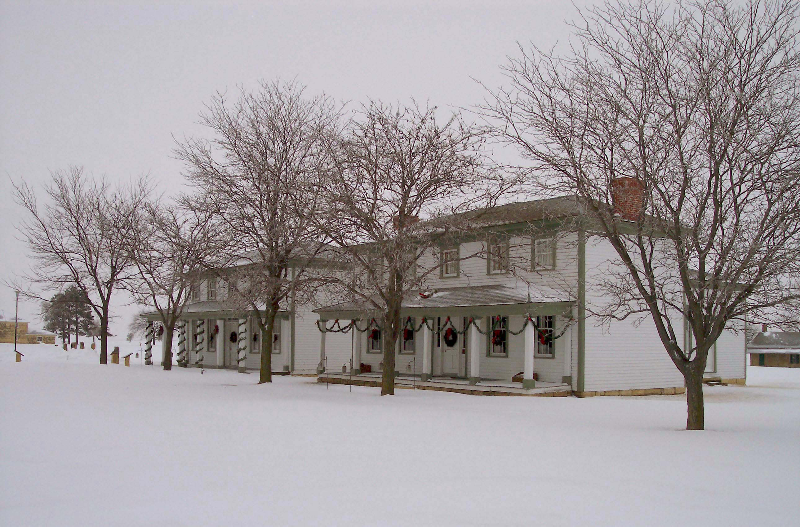 Exterior of Fort Hays officers' quarters, decorated for Christmas with snow on ground.
