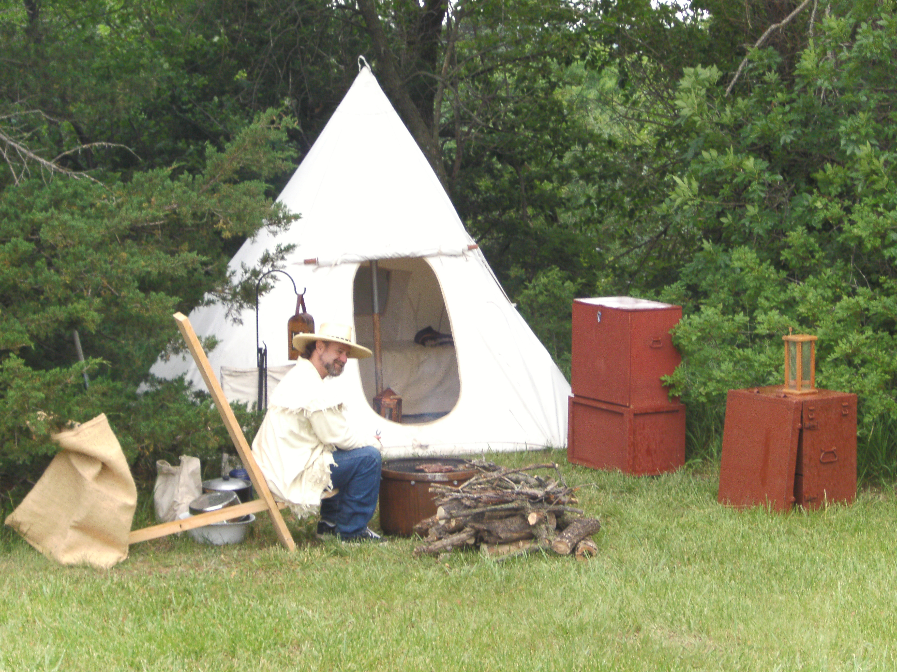 Male reenactor as a trader, sitting in front of tipi