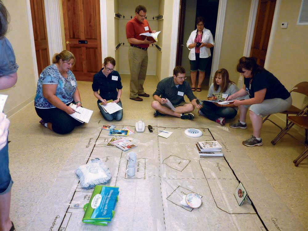 Teachers working on mock archeology excavation site drawn on classroom floor