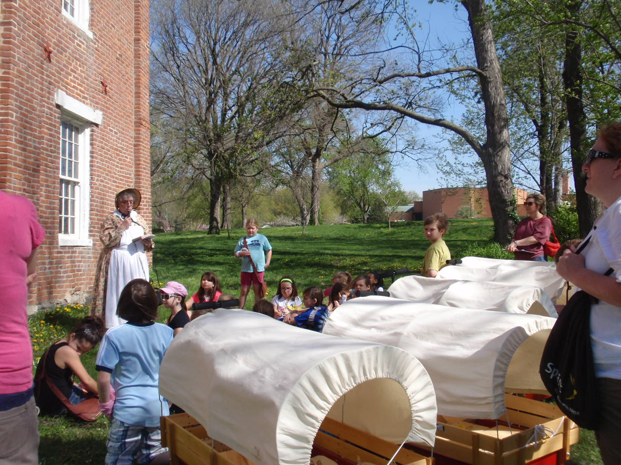 Studentswith covered wagons in front of Shawnee Indian Mission State Historic Site.