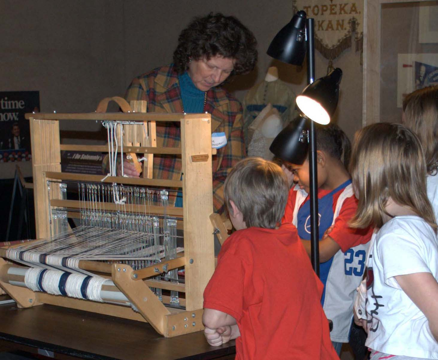 Demonstration of table top loom as students watch.