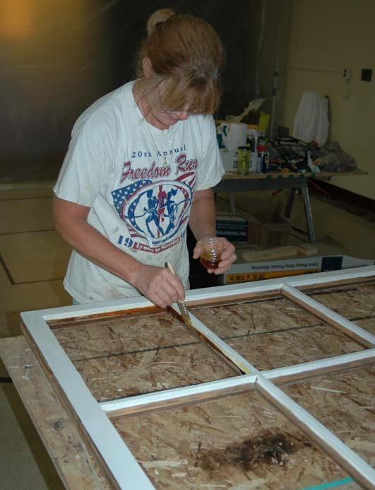 Woman applying linseed oil to wooden window frame.