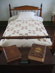 Two family Bibles setting on bench at end of quilted bed