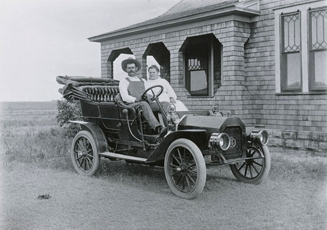 L. W. Halbe photograph, 1911,  of D. J. Heinze and his wife  seated in an Reo convertible automobile parked next to their home in  Russell County, Kansas.