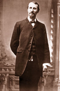 Fashionable Fred Harvey wears a frock coat, vest and pocket watch.