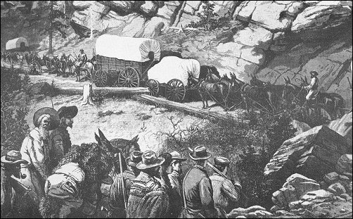 [Wagons struggling up a narrow mountain road.]
